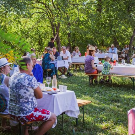 Groups enjoying dinner outside at a celebration the Angofa Wildlife Centre, eating traditional Romanian meals that highlight local sustainable agriculture