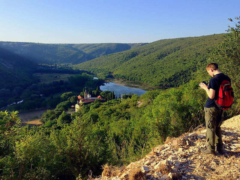 Photo of a person hiking at a viewpoint in Krka, using GIS to record conservation data
