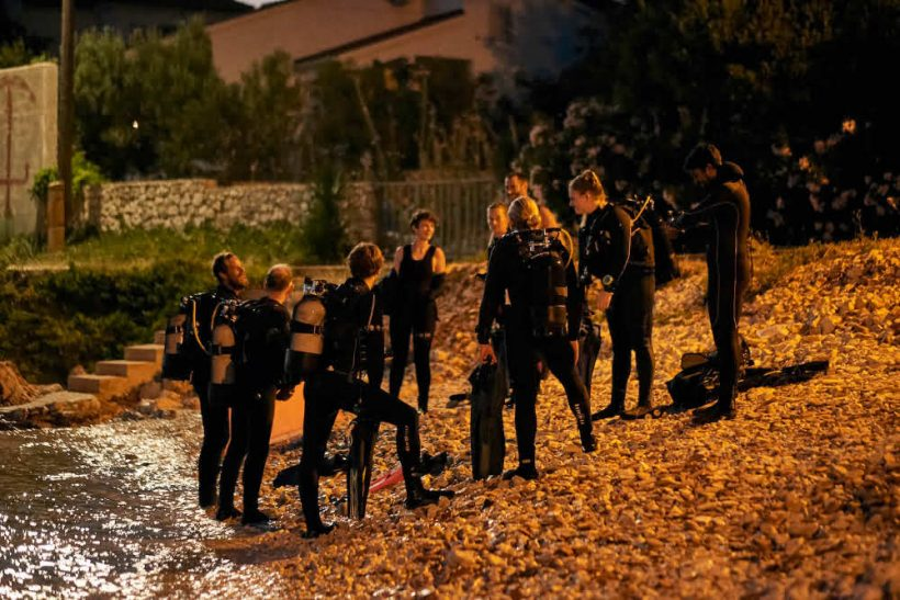 Group of divers on the beach in Silba, taking PADI NAUI scuba diving qualification courses at the Silba Island Marine Research Centre's Dive School in Croatia